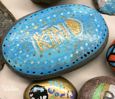 Rock painted with the word kind surrounded by other rocks.