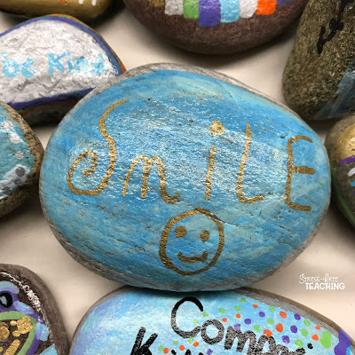 Rock painted with the word smile surrounded by other painted rocks.